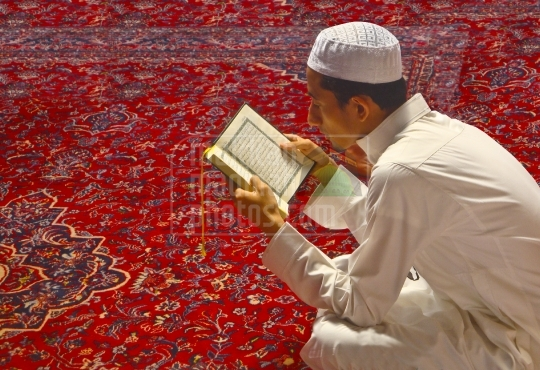 A young man reciting Qur'am inside Holy Mosque