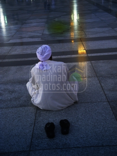 A Pilgrim sitting on the piazza near green dome.